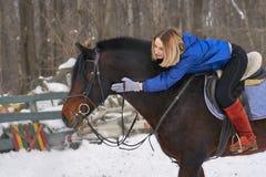 En ung flicka med vitt hår rider en häst Flickan kramar hennes favorit- häst molnig dagvinter Arkivfoto