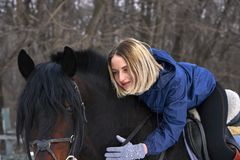 En ung flicka med vitt hår rider en häst Flickan kramar hennes favorit- häst molnig dagvinter Närbild Royaltyfri Fotografi