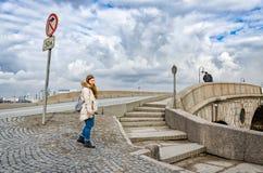 En ung flicka nära den Prachechny bron på en molnig vårdag Royaltyfri Bild