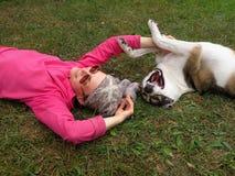 En ung flicka och en hund är på gräs Arkivbild