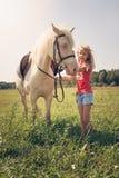 En ung flicka och en vit ponnyhäst royaltyfri bild
