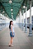 En ung flicka på en drevstation nära det blåa drevet royaltyfri foto
