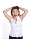 En ung flicka på en isolerad vit bakgrund som skriker i frustration som drar hennes hår på hennes huvud arkivfoton