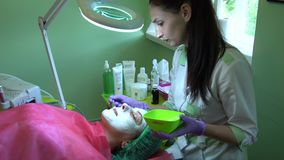 En ung flicka på ett mottagande med en cosmetologistThe cosmetologist sätter en maskering på hans framsida stock video