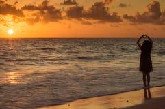 En ung flicka på stranden som gör en förälskelsehjärta på den guld- timmen fotografering för bildbyråer