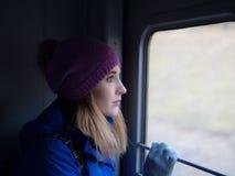 En ung flicka reser på ett drev arkivbild