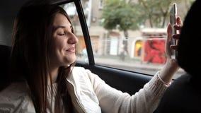 En ung flicka rider i bilen, meddelar via den videopd appellen på en mobiltelefon lager videofilmer