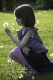 En ung flicka rymmer en maskros som hon har precis valt Arkivfoton