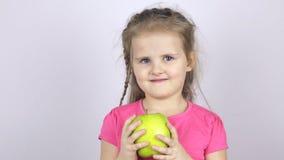 En ung flicka rymmer ett stort grönt äpple lager videofilmer