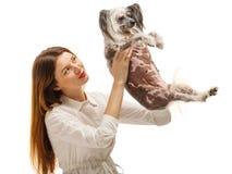 En ung flicka rymmer en rolig kines krönad hund och kastar upp den bakgrund isolerad white inomhus royaltyfria bilder