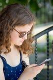 En ung flicka rymmer en telefon i hennes händer Kommunikation genom att använda en smartphone Modern underhållning på Internet_en royaltyfria bilder
