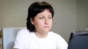 En ung flicka ser in i datorskärmen och drinkteet En kvinna arbetar på internet till och med en bärbar dator lager videofilmer