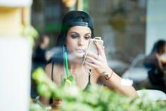 En ung flicka sitter bara i ett kafé, lyssnar till musik på hörlurar och kontrollerar sminket till och med a-smartphonen arkivbild