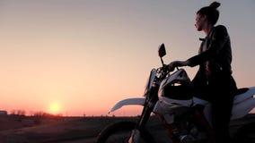 En ung flicka sitter grensle en motorcykel och h?ller ?gonen p? den h?rliga solnedg?ngen arkivfilmer