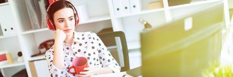 En ung flicka sitter i hörlurar på en tabell i kontoret, rymmer en röd kopp i henne händer och ser bildskärmen arkivfoton