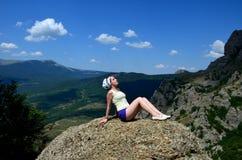 En ung flicka sitter på en enorm sten med hennes stängda ögon, hennes händer lutar bakom Koppla av som omges av berg i ljust soll royaltyfri bild