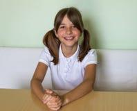 En ung flicka sitter på ett skrivbord Arkivbild
