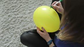 En ung flicka sitter på en grå matta och drar ett leende på en gul ballong stock video