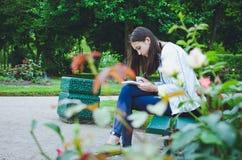 En ung flicka sitter på parkerar bänken royaltyfri fotografi