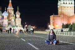 En ung flicka sitter på röd fyrkant i Moskva arkivbild