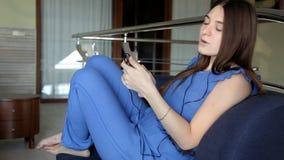 En ung flicka sitter på en soffa sätter hörlurar lyssnar till musik och sjunger på lager videofilmer