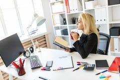 En ung flicka sitter på en tabell i kontoret och att rymma en kopp och en läsning en bok royaltyfri fotografi