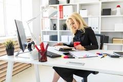 En ung flicka sitter på en tabell i kontoret och att rymma en kopp och en läsning en bok fotografering för bildbyråer