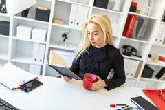 En ung flicka sitter på en tabell i kontoret och att rymma en kopp och en läsning en bok arkivbilder