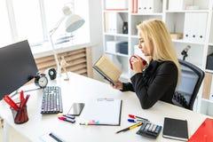 En ung flicka sitter på en tabell i kontoret och att rymma en kopp och en läsning en bok arkivfoto