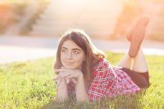 En ung flicka sitter utomhus på gräset i ett träd som utomhus grubblar blick, en sommardag i parkera Royaltyfri Bild