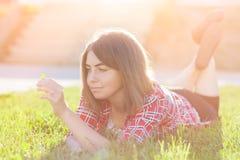 En ung flicka sitter utomhus på gräset i ett träd som utomhus grubblar blick, en sommardag i parkera Arkivbild