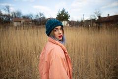 En ung flicka som b?r ett pastellf?rgat lag och en stilfull hatt, poserar i ett vetef?lt royaltyfria bilder