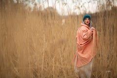 En ung flicka som b?r ett pastellf?rgat lag och en stilfull hatt, poserar i ett vetef?lt Tillbaka viev arkivfoton