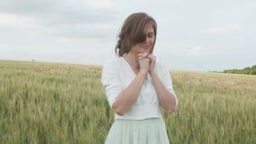 En ung flicka som ber i ett vetefält, en kvinna bland öron av havre som tycker om naturen och tackar guden, ett begrepp av religi lager videofilmer