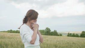 En ung flicka som ber i ett vetefält, en kvinna bland öron av havre som tycker om naturen och tackar guden, ett begrepp av religi stock video