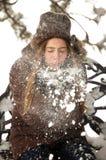 En ung flicka som blåser snö ut ur hennes tumvanten Fotografering för Bildbyråer