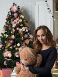 En ung flicka som framme sitter av en julgran och kramar en leksakbjörn Anden av jul och en avkänning av beröm arkivfoto