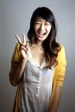 En ung flicka som gör ett fredtecken. Arkivfoton