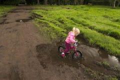 En ung flicka som lär att cykla royaltyfria bilder