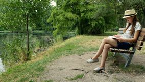En ung flicka som läser en bok på en bänk nära sjön royaltyfri fotografi