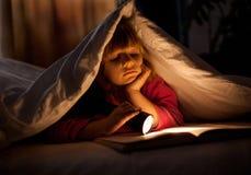 En ung flicka som läser en bok under räkningarna med en ficklampa Arkivfoton
