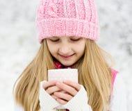 En ung flicka som rymmer en kopp av varmt drink och le royaltyfri fotografi