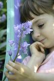 En ung flicka som rymmer en stam av blåklockan, blommar royaltyfri bild