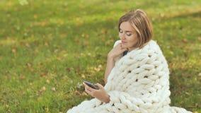 En ung flicka som slås in i en merinoplädmaskinskrivning på telefonen som ett meddelandesammanträde på gräset i en stad parkerar arkivfilmer