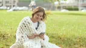 En ung flicka som slås in i en merinoplädmaskinskrivning på telefonen som ett meddelandesammanträde på gräset i en stad parkerar lager videofilmer