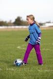 En ung flicka som sparkar en fotbollboll Arkivbilder