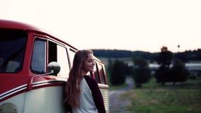 En ung flicka som står y en bil på en roadtrip till och med bygd lager videofilmer