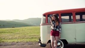 En ung flicka som står y en bil på en roadtrip till och med bygd stock video