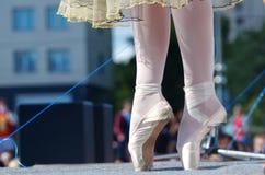En ung flicka står på pointe på en utomhus- gataplats Fritt tillträde för fotografi arkivfoton