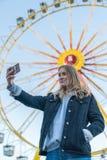 En ung flicka tar en selfie framme av en karusell på hamburgareDomna royaltyfria bilder